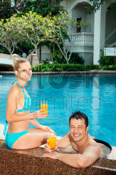 man and woman relaxing at the edge of pool with glasses of orange juice stock photo