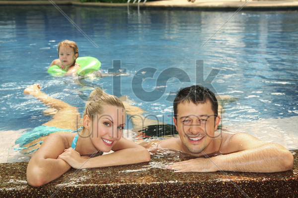 man and woman relaxing at the edge of pool stock photo