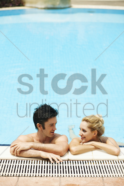 man and woman relaxing in pool stock photo