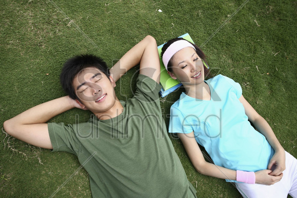 man and woman relaxing on the field, eyes closed stock photo