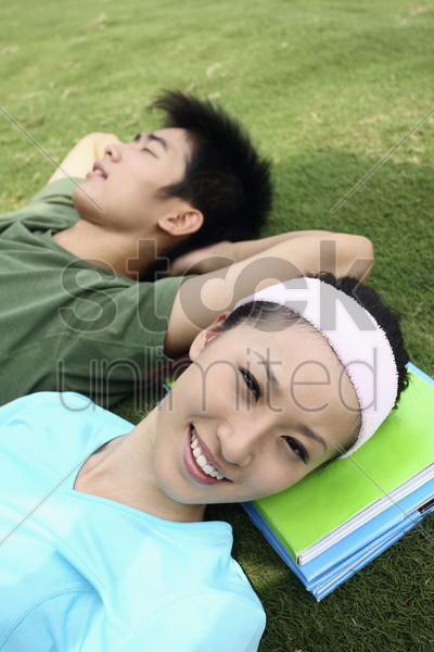 man and woman relaxing on the field stock photo
