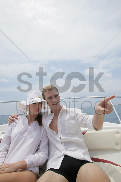man and woman resting on speedboat stock photo