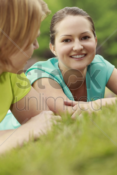 man and woman resting on the grass stock photo