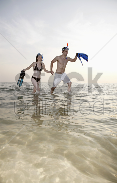 man and woman running on beach with snorkeling gear stock photo