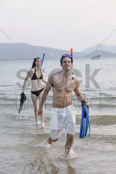 man and woman running through water, holding flippers stock photo