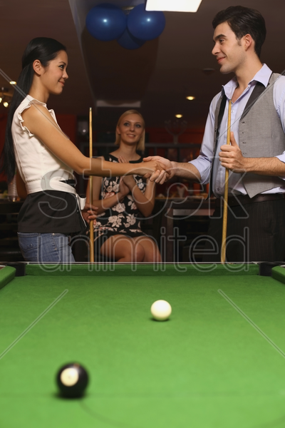 man and woman shaking hands after the game stock photo