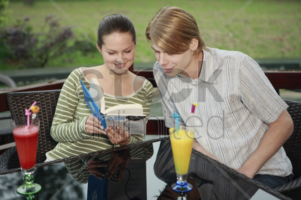 man and woman sharing a book stock photo