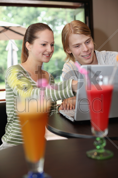 man and woman sharing a laptop stock photo