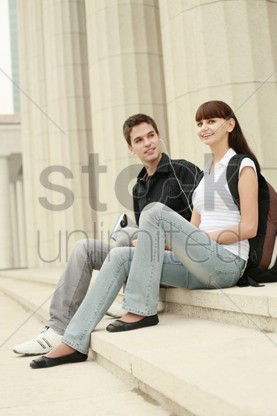 man and woman sharing a portable mp3 player stock photo