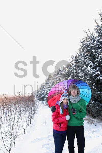 man and woman sharing an umbrella stock photo