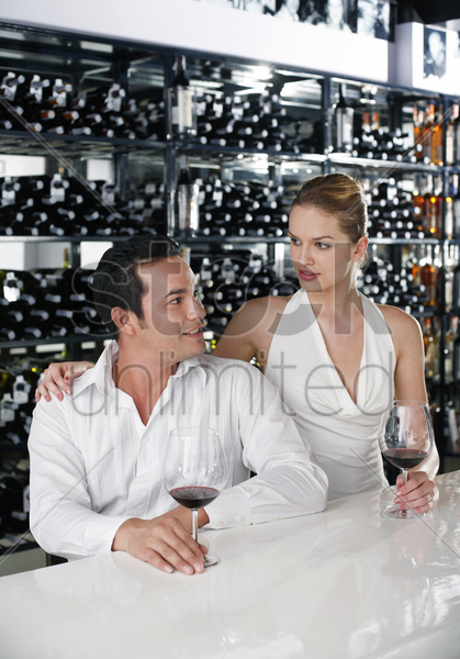man and woman sitting at bar counter talking stock photo