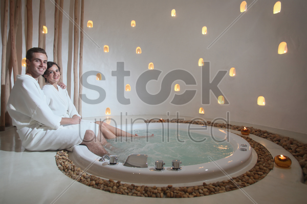 man and woman sitting by the hot tub stock photo