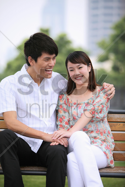 man and woman sitting on a bench, smiling stock photo