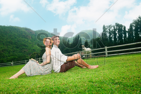 man and woman sitting on grass stock photo