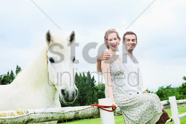 man and woman sitting on wooden fence stock photo