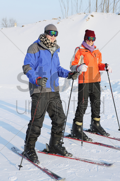 man and woman skiing stock photo