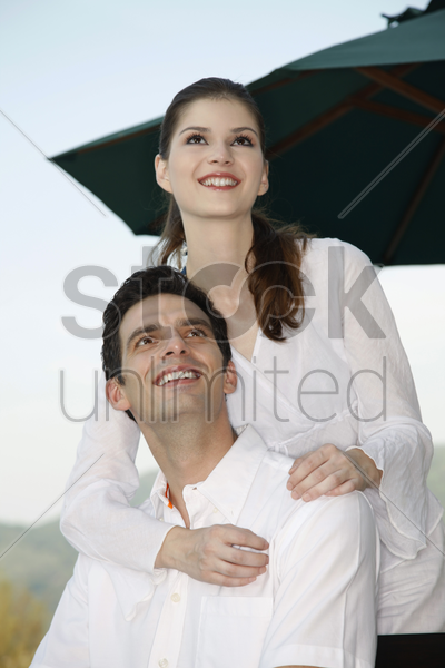 man and woman smiling and looking up stock photo