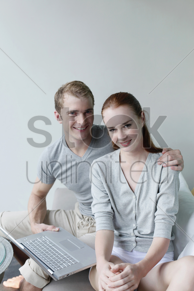 man and woman smiling, laptop on man's lap stock photo