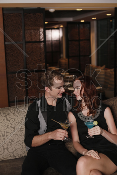 man and woman smiling while looking at each other stock photo