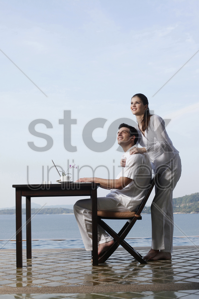 man and woman smiling while looking up stock photo