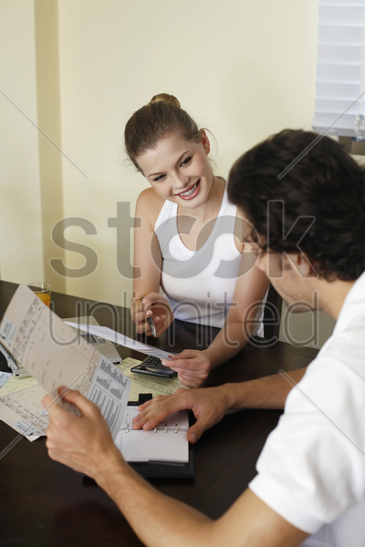 man and woman sorting out bills together stock photo
