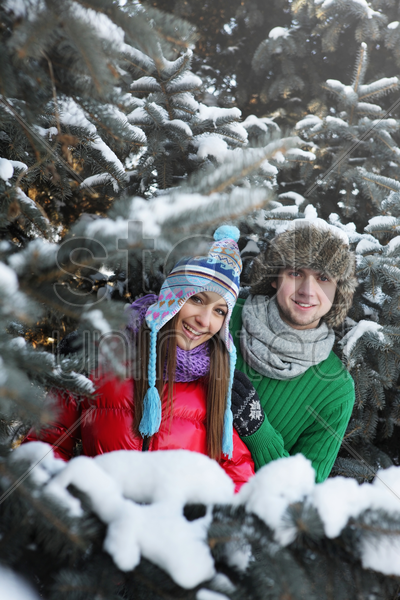 man and woman standing among the snow covered trees stock photo