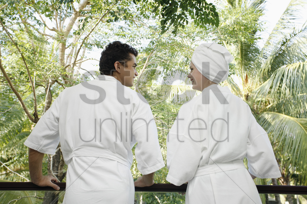 man and woman standing at the balcony, looking at each other stock photo