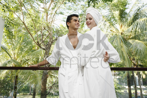 man and woman standing at the balcony stock photo