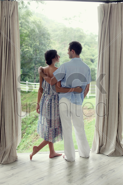 man and woman standing by the glass window, looking at each other stock photo