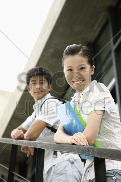man and woman standing on the stairs, smiling at the camera stock photo