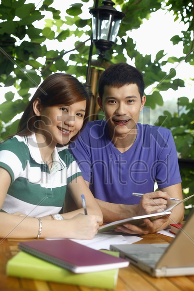 man and woman studying together stock photo