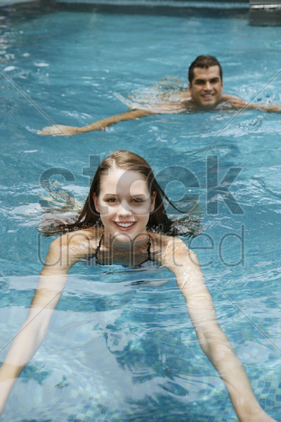 man and woman swimming in the pool stock photo
