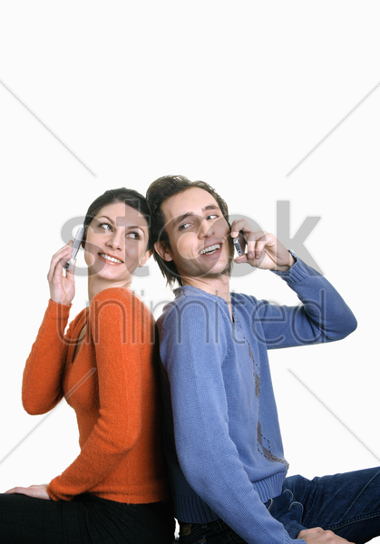 man and woman talking on their cell phones stock photo