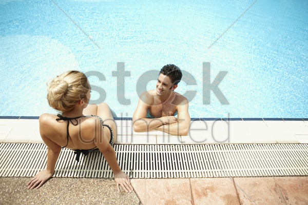man and woman talking while relaxing by the poolside stock photo