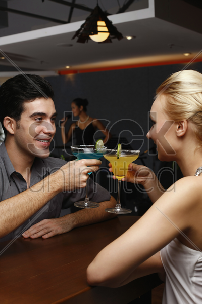 man and woman toasting drinks stock photo
