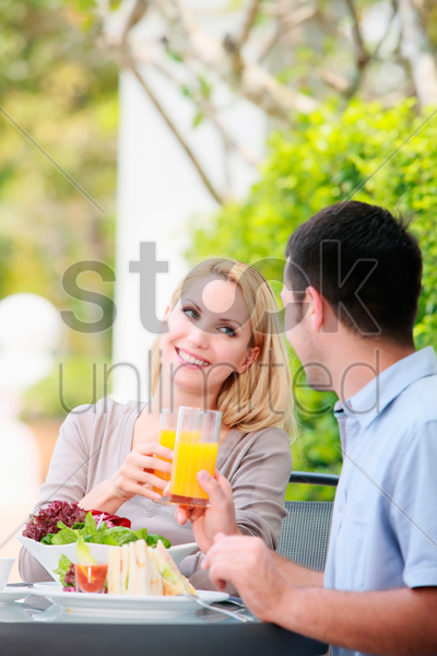 man and woman toasting orange juice at an outdoor restaurant stock photo