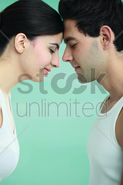 man and woman touching foreheads stock photo