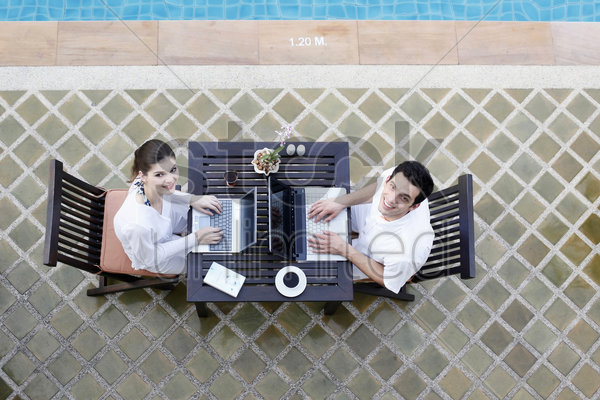 man and woman using laptop by the pool side stock photo