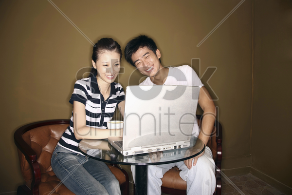 man and woman using laptop, laughing stock photo