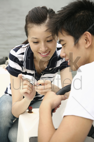 man and woman viewing their pictures on the camera while traveling on the boat stock photo