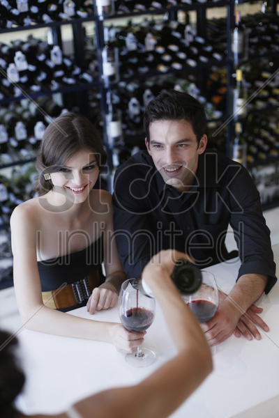 man and woman waiting for their wine to be poured stock photo