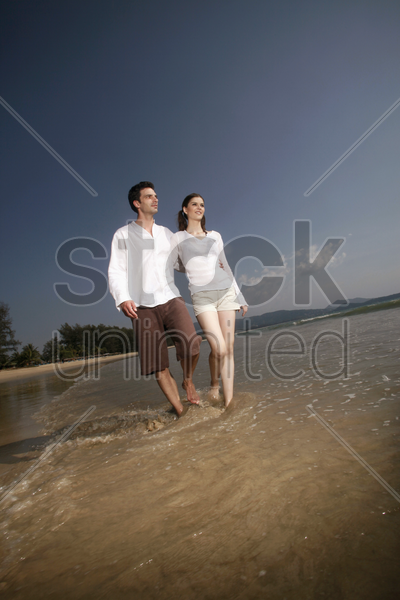 man and woman walking along the beach stock photo