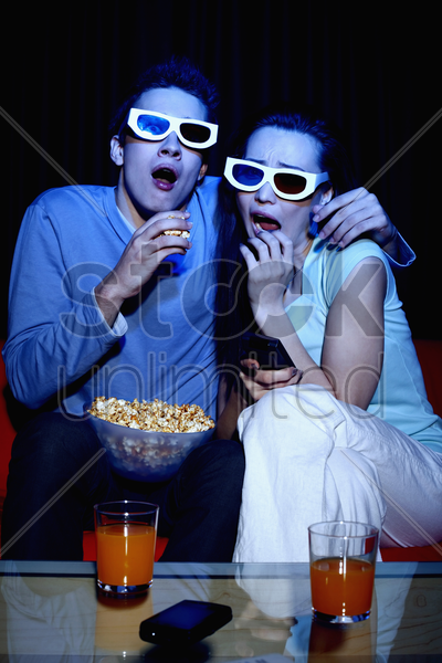 man and woman watching 3d movie stock photo