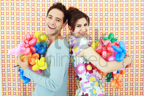 man and woman with sculpted balloons stock photo