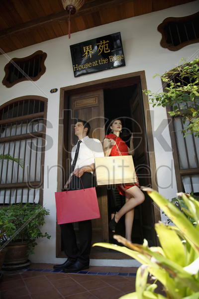 man and woman with shopping bags standing at the doorway stock photo