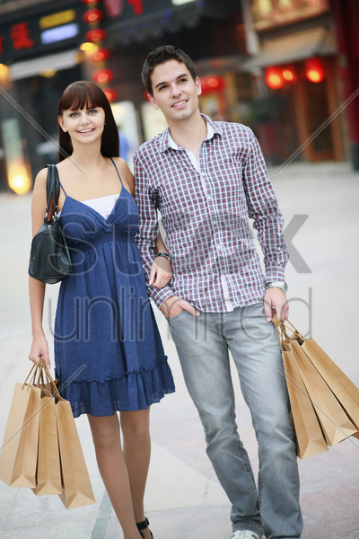 man and woman with shopping bags stock photo