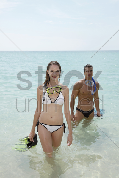man and woman with snorkeling gear on beach stock photo