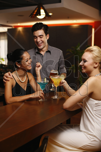 man and women drinking and chatting at a bar stock photo