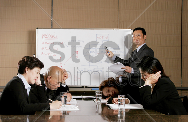 man and women falling asleep after listening to a dull presentation by the manager stock photo