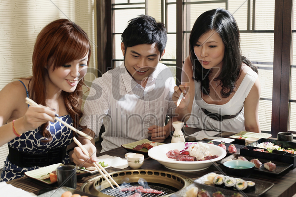 man and women grilling beef in a restaurant stock photo